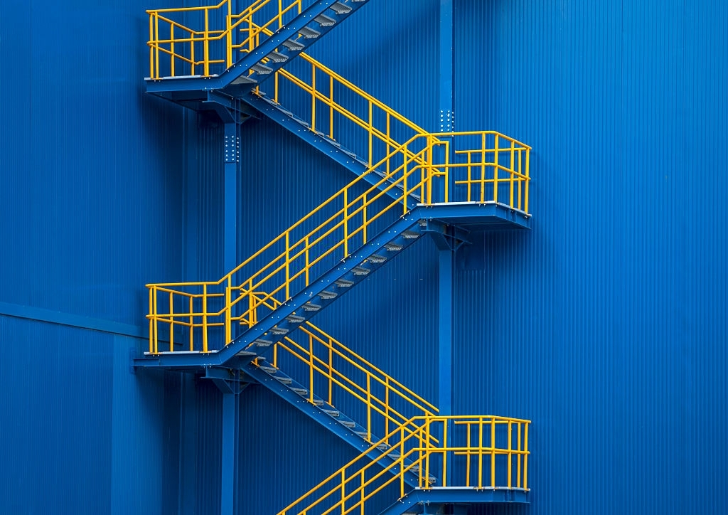 Yellow metal staircase against a blue wall in factory